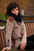 坐在长凳上的黑头发的年轻美丽女士 — 图库照片