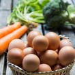 Eggs in basket and vegetables — Stock Photo