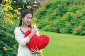 Asian woman holding a red heart — Stock Photo