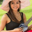 Asian woman playing ukulele — Stock Photo
