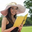 Beautiful young woman reading book at park — ストック写真