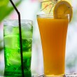 Green fruit soda and orange juice — Stock Photo