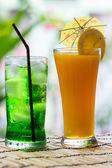 Green fruit soda and orange juice — Stock Photo