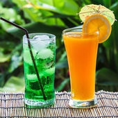 Green soda and orange juice — Stok fotoğraf