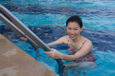 Portrait of Asian woman getting out of a swimming pool — Stock Photo