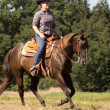 Stock Photo: Outdoor Ride - young Womon brown Quarter Horse