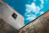Byggnad med gamla fönster mot himlen — Stockfoto