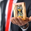 Man in a suit with tie holding an hourglass — Stock Photo