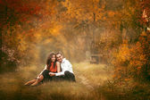 Beautiful couple sitting in a autumn park and embraces — Stock Photo