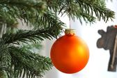 Orange Christmas bauble on branch — Stock Photo