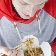 Man eating take away noodles — Stock Photo