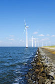 Energia alternativa por moinhos de vento perto da água — Fotografia Stock