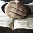 Hands praying on bible — Stock Photo
