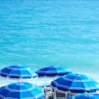 Concept of holiday blue beach with parasols in Nice — Stock Photo