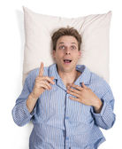 Man in bed on pillow — Stock Photo