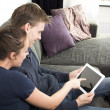 Happy couple on couch with tablet pc — Stock Photo