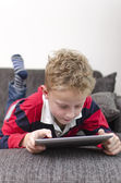 Boy on couch playing with iPad — Stock Photo