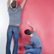 Man and wife wallpapering — Stock Photo