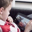 Постер, плакат: Boy watching movie on iPad