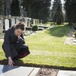 Stock Photo: Womsitting at grave