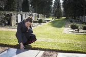 Woman sitting at grave — Stock Photo