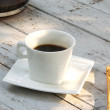 Cup of coffee over grunge wooden background — Stock Photo