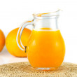 Orange juice in pitcher and orange on white background — Stockfoto