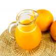 Orange juice in pitcher and orange on white background — ストック写真