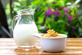 Copos de maíz en el tazón de fuente blanco y la leche en la mesa de madera — Foto de Stock
