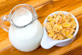 Corn flakes in white bowl and milk on wooden table — Stock Photo