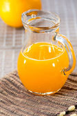 Orange juice in glass jug — Stock Photo
