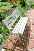 White bench in garden — Stock Photo