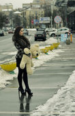 Girl with a teddy bear on a street — Stock Photo