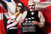 Woman and man in mask skull face with movie board slapstick — Stock Photo