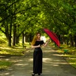Girl in a black dress with umbrella in the park — Stock Photo