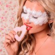 Lady in white mask eating cookie — Stock Photo #32068453