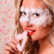 Lady in white mask eating cookie — Stock Photo