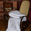 Stock Photo: Rocking chair with coverlet near fireplace