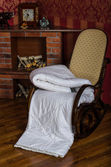 Rocking chair with coverlet near the fireplace — Stock Photo