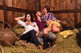 Girls posing with a young guy in the hay — Stock Photo