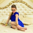Girl in a blue dress  sitting on a bed — Stock Photo
