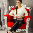 Girl sitting on a red vintage chair — Stock Photo