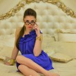 Girl in a blue dress sitting on a bed — Stock Photo #36031933
