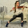 Girl  playing the violin on a leather couch  — Foto Stock