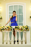 Beautiful girl in glasses posing on a balcony with flowers — Stock Photo