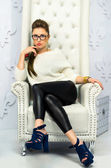 Girl in glasses sitting on a leather armchair — Stock Photo