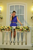 Beautiful girl in glasses posing on a balcony with flowers — 图库照片