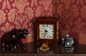 Retro clock, elephant figurines and camera — Stock fotografie