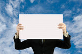 Businessman holding blank sign in sky — Stock Photo
