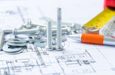 Nuts and bolts over architectural plan — Stock Photo